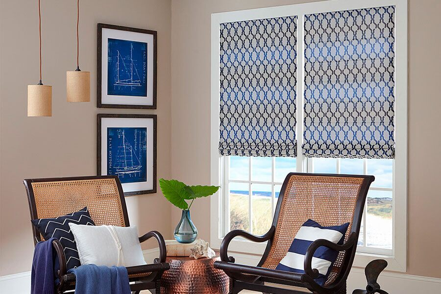 Modern nautical themed living room corner featuring two wicker accent folding chairs with navy and white throw pillows, sailboat design drawings on one wall next to chairs and large double-hung windows with patterned roller shades on other wall.